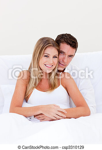 Portrait of an enamored couple sitting on bed - csp3310129