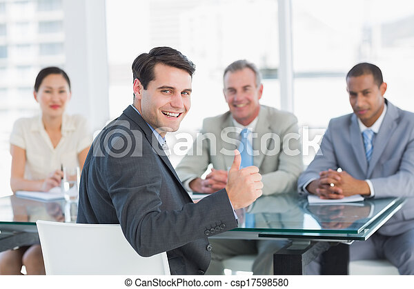 Portrait of an executive gesturing thumbs up with recruiters during a job interview at office - csp17598580