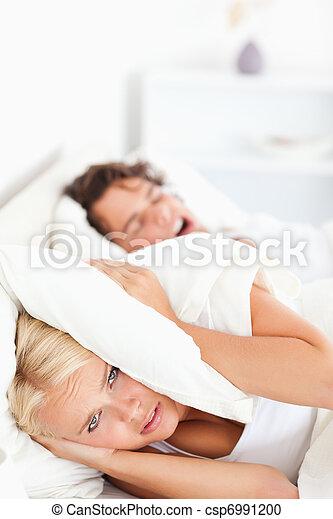 Portrait of an unhappy woman awaken by her fiance's snoring - csp6991200