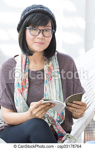 portrait of beautiful asian woman relaxing time reading book on cradle happiness emoton with smiling face - csp33178764