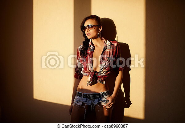portrait of beautiful fashion sexy brunette girl in jeans and colorful shirt in glasses behind sunset indoors - csp8960387