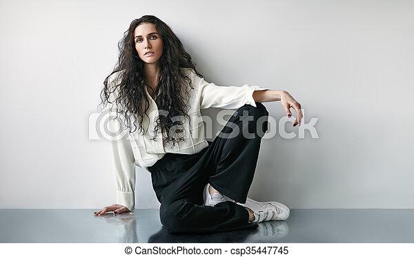 Portrait of beautiful fashion woman sitting on the floor - csp35447745