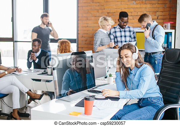 Portrait of beautiful happy young manager sitting in headphones at office desk - csp59230057