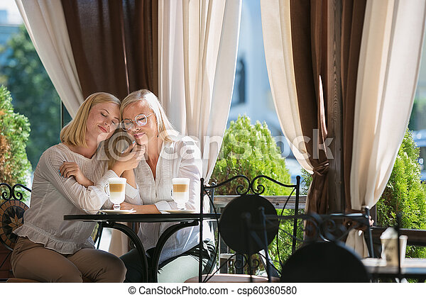 Portrait of beautiful mature mother and her daughter holding cup sitting at home - csp60360580
