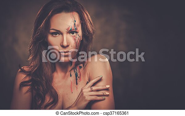 Portrait of beautiful woman with creative colored makeup on a dark background. - csp37165361