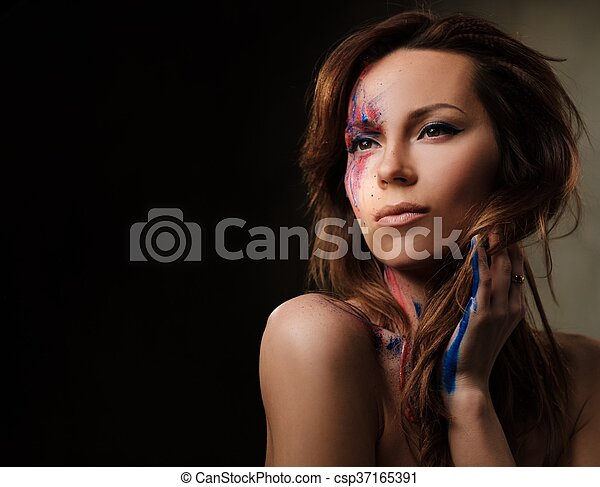 Portrait of beautiful woman with creative colored makeup on a dark background. - csp37165391