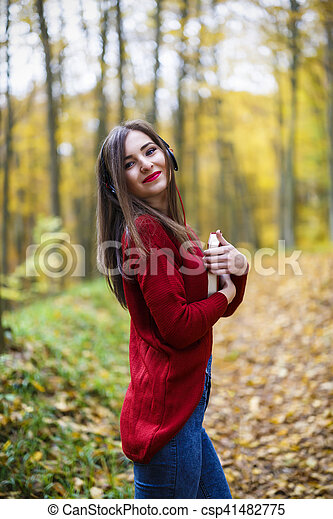 Portrait of beautiful young brunette woman reading a book in the park at fall. - csp41482775