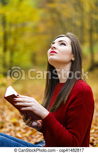 Portrait of beautiful young brunette woman reading a book in the park at fall. - csp41482817