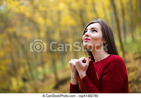 Portrait of beautiful young brunette woman reading a book in the park at fall. - csp41482780