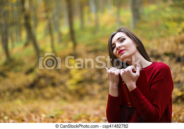 Portrait of beautiful young brunette woman reading a book in the park at fall. - csp41482782