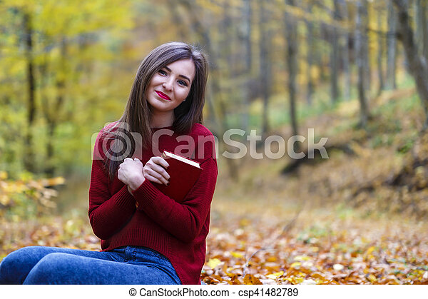 Portrait of beautiful young brunette woman reading a book in the park at fall. - csp41482789