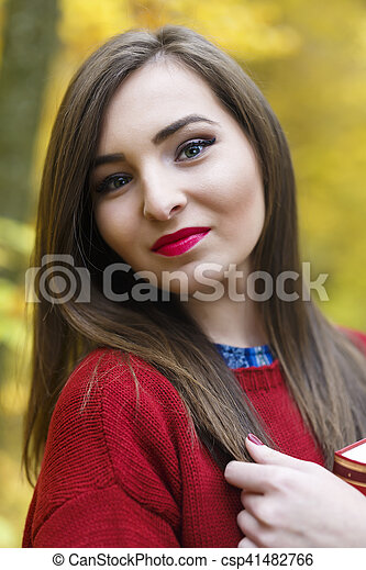 Portrait of beautiful young brunette woman reading a book in the park at fall. - csp41482766