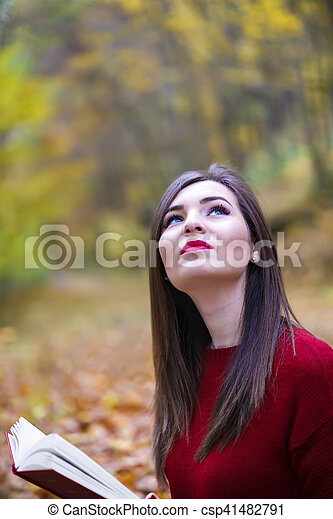 Portrait of beautiful young brunette woman reading a book in the park at fall. - csp41482791