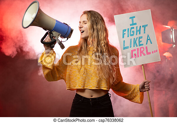 portrait of blond young girl with megaphone promoting feminism - csp76338062