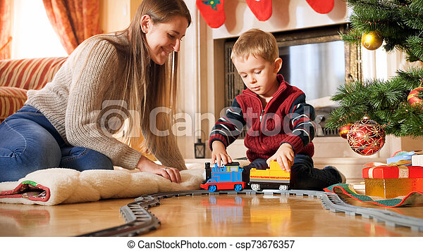 Portrait of boy with his mother playing on floor with toy train and railways. Child receiving presents and toys on New Year or Xmas - csp73676357