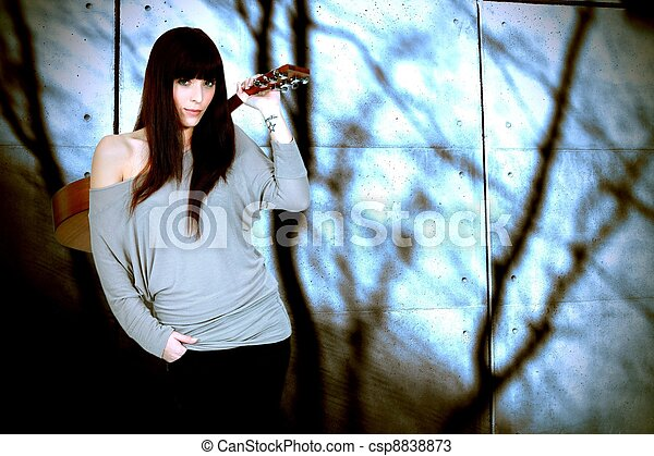 Portrait Of Brunette Carrying Guitar On Her Back Stock Photo