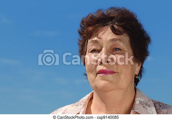 portrait of brunette pensioner woman outdoor, blue sky - csp9140085