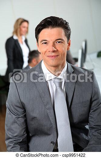 Portrait of businessman sitting in meeting room - csp9951422