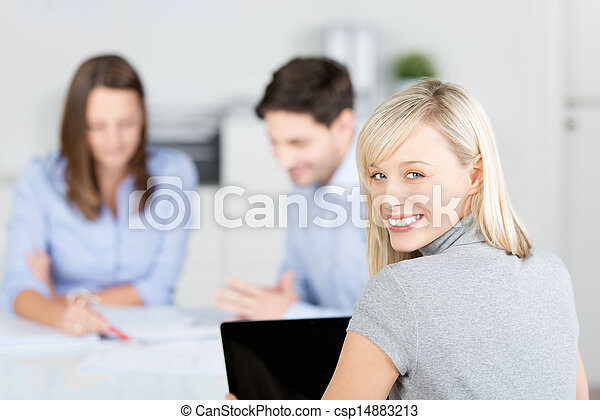 Portrait of businesswoman looking over shoulder with colleagues discussing in meeting at conference desk - csp14883213