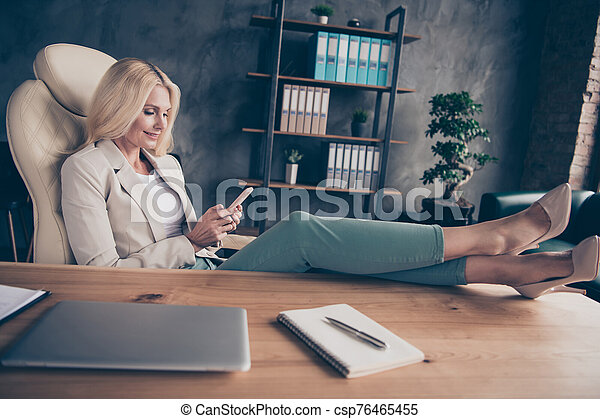 Portrait of charming middle aged blonde hair woman use cellphone have chat with her workforce career partners type messages sit in chair put her high-heels on wooden table - csp76465455