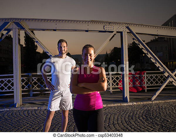 portrait of couple jogging across the bridge in the city - csp53403348