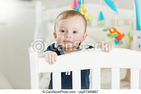 Portrait of cute baby boy standing in white wooden crib and looking in camera - csp57469867