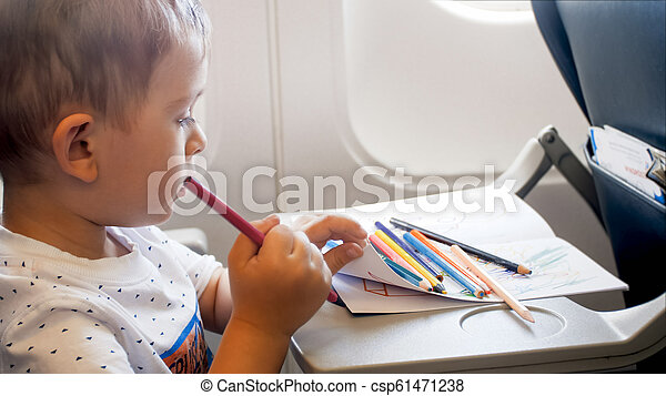 Portrait Of Cute Little Boy Drawing In Copybook During Long Flight In Airplane Portrait Of Little Boy Drawing In Copybook