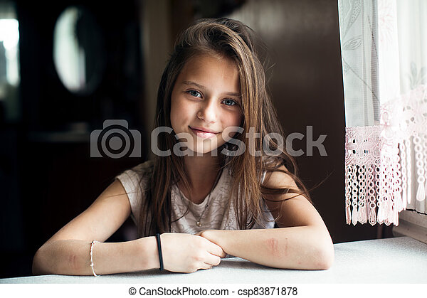 Portrait of cute little girl sitting at the table. - csp83871878