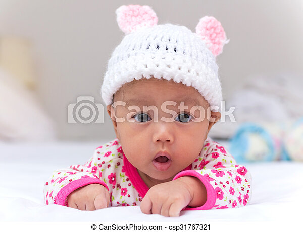 4681df359 Portrait of cute newborn baby girl on the bed.
