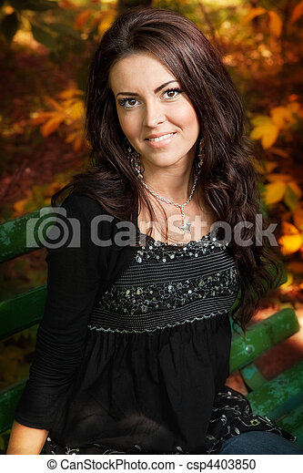 Portrait of cute young woman in autumn park - csp4403850