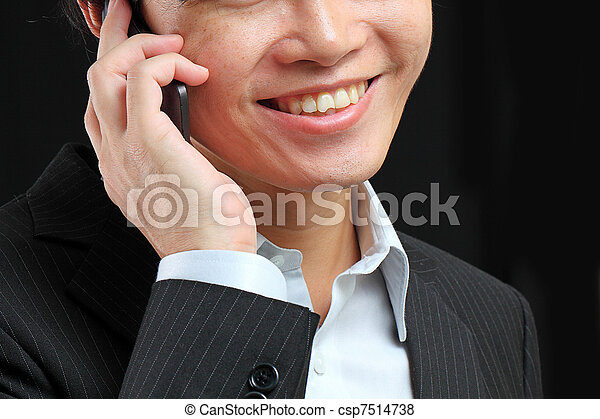 portrait of e young man talking on mobile against a black background - csp7514738