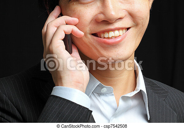portrait of e young man talking on mobile against a black background - csp7542508