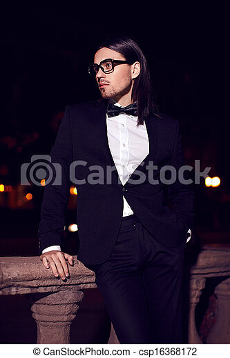 1d18c99e41d Portrait Of Fashion Elegant Long-Haired Young Caucasian Sexy Muscled  Attractive Handsome Man Model Businessman In Black Costume With Moustache  In The Street ...
