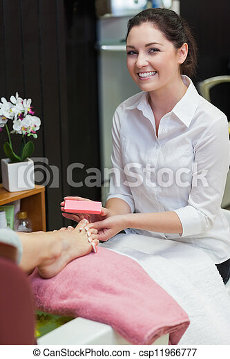 Portrait of female buffering toe nails at spa center - csp11966777