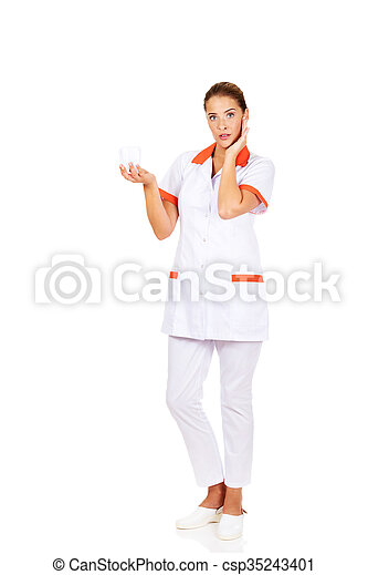 Portrait of female dentist holding a tooth model - csp35243401