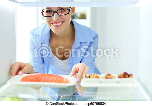 Portrait Of Female Standing Near Open Fridge Full Of Healthy Food Vegetables And Fruits