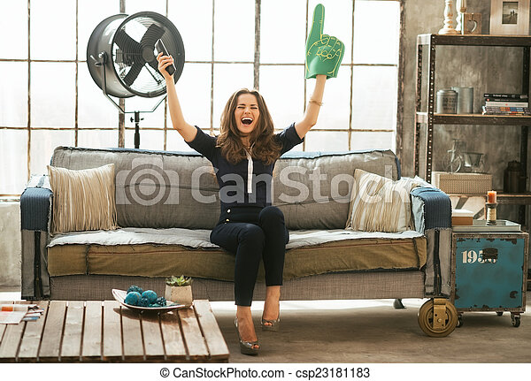 Portrait of football fan woman watching tv in loft apartment and - csp23181183