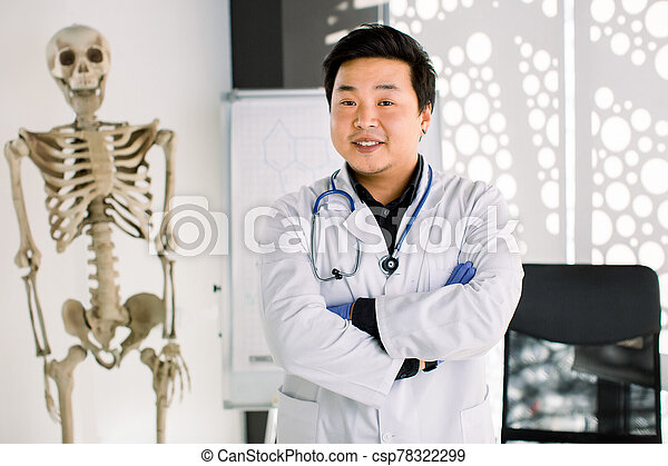 Portrait of friendly Asian Korean doctor man at his office smiling to camera. Young smiling clinician in white coat crossing arms on chest, human skeleton on the background - csp78322299