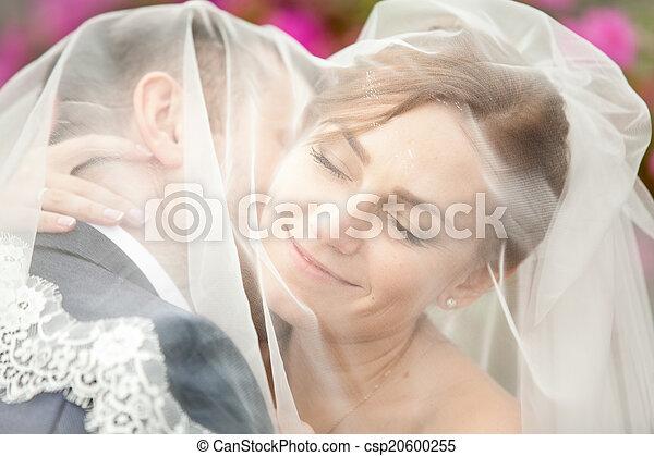 Portrait of groom kissing bride in neck under veil - csp20600255