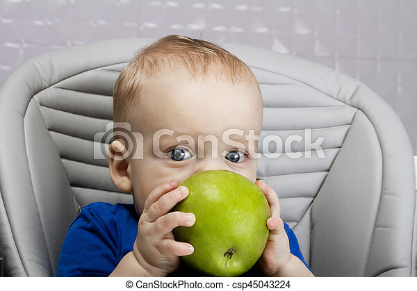 Portrait of handsome 9-month-old boy with a big green apple sitting in the baby chair - csp45043224