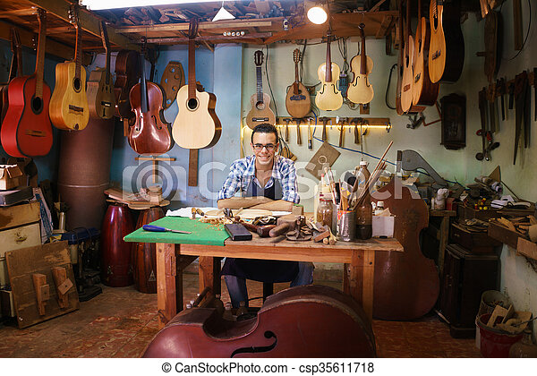 Portrait Of Happy Artisan Lute Maker In Guitar Shop Smiling At Camera - csp35611718
