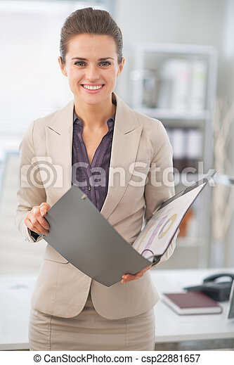 Portrait of happy business woman with documents in office - csp22881657
