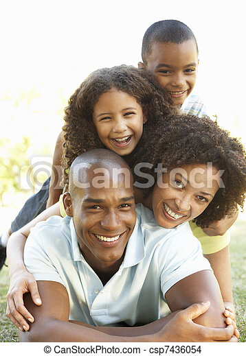 Portrait of Happy Family Piled Up In Park - csp7436054
