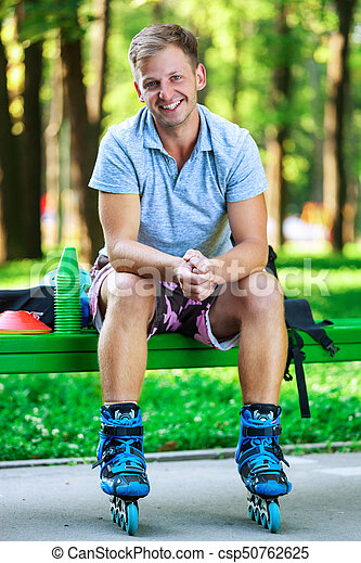 Portrait of happy handsome male roller sitting on bench in the park. - csp50762625