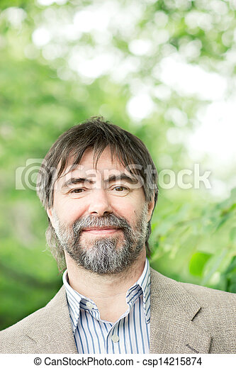 Portrait of happy middle-aged businessman looking at camera and smiling, outdoors - csp14215874
