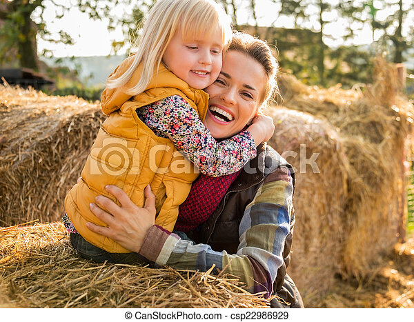 Portrait of happy mother and child hugging while on haystack - csp22986929