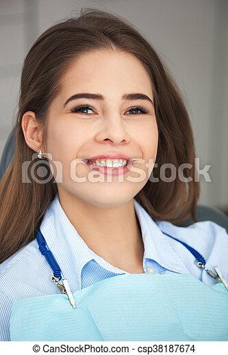 Portrait of happy patient in dental chair. - csp38187674