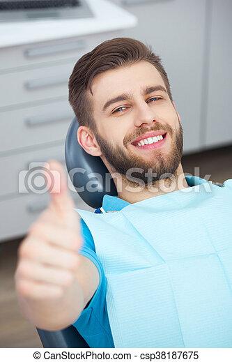 Portrait of happy patient in dental chair. - csp38187675