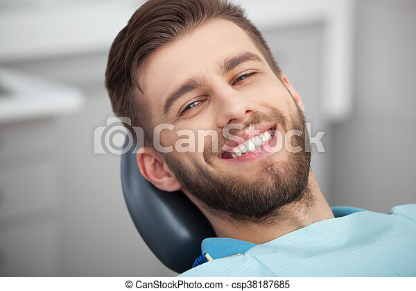 Portrait of happy patient in dental chair. - csp38187685