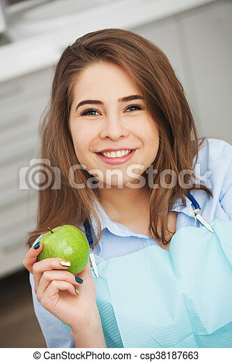 Portrait of happy patient in dental chair with green apple. - csp38187663